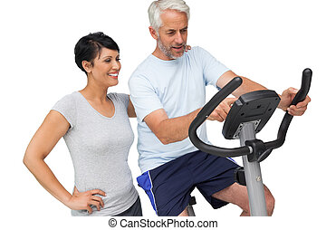 Happy woman looking at mature man on stationary bike over...