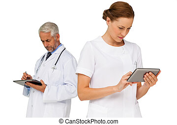 Male and female doctors using digital tablets over white...