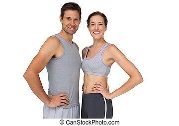 Portrait of a happy fit couple with hands on hips - Portrait...