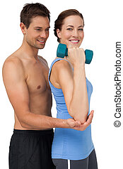 Male trainer assisting woman with dumbbell
