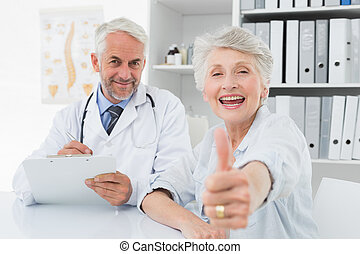 Happy senior patient gesturing thumbs up with doctor -...