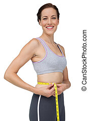 Portrait of a fit woman measuring waist