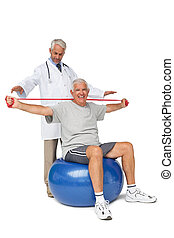 Male physiotherapist looking at senior man sit on exercise ball with yoga belt over white background