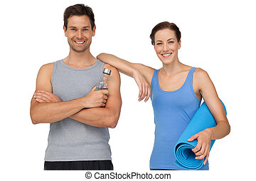 Fit young couple with exercise mat and water bottle -...