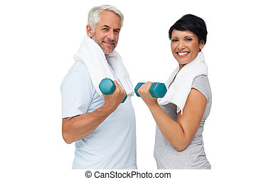 Fit mature couple exercising with dumbbells - Portrait of a...