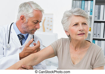 Male doctor injecting senior patient