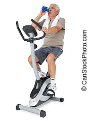 Senior man drinking water on stationary bike - Full length...