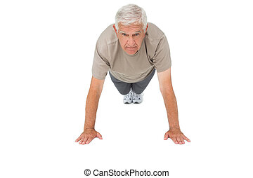 Portrait of a senior man doing push ups over white...