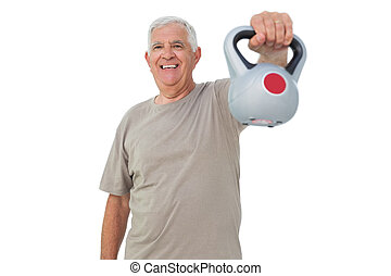 Portrait of a senior man exercising with kettle bell over...