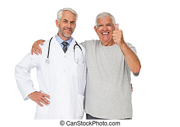 Portrait of a doctor with senior man gesturing thumbs up...