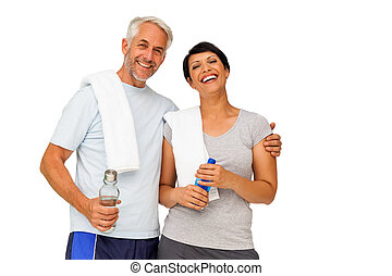 Portrait of a happy fit couple standing over white...