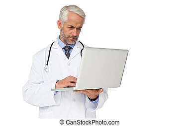 Concentrated male doctor using laptop over white background