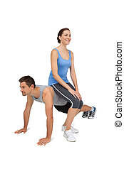 Female trainer sitting on man as he does push ups - Full...