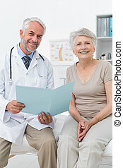 Male doctor and senior patient with reports - Portrait of a...