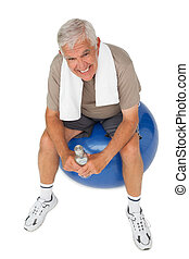 Happy senior man with water bottle sitting on fitness ball -...