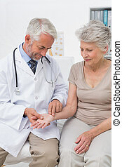 Male doctor taking a senior females pulse at the medical...