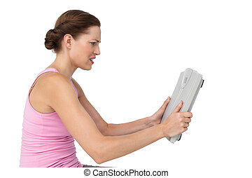 Annoyed young woman with weight scale