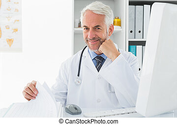 Mature male doctor with computer at medical office -...