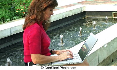 Woman Typing by Fountain - Close-up of female working on...