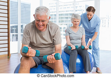Female therapist assisting senior couple with dumbbells in...