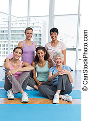 Happy sporty women sitting in yoga class - Full length...
