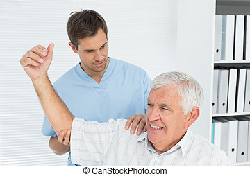 Physiotherapist assisting senior man to stretch his hand