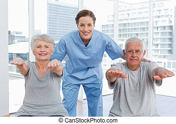 Female therapist assisting senior couple with exercises -...