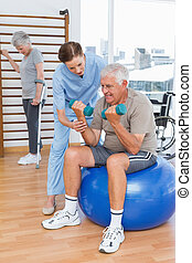Therapist assisting senior man with dumbbells - Female...