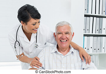 Portrait of a female doctor with happy senior patient at the...