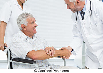 Smiling senior patient and doctor shaking hands - Side view...