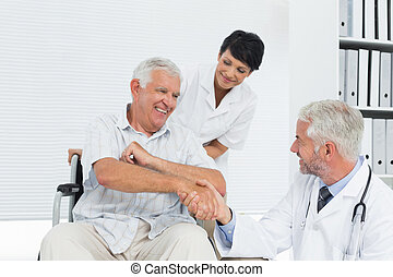Happy senior patient and doctor shaking hands in the medical...