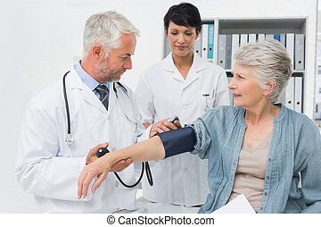 Doctor measuring blood pressure of a senior patient - Male...