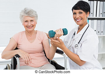 Physiotherapist assisting senior woman to lift dumbbell -...