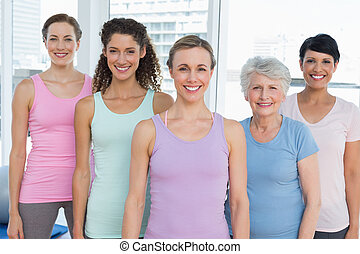 Smiling women standing in yoga class - Portrait of smiling...