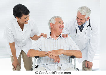 Happy senior patient with doctors sitting in wheelchair at...
