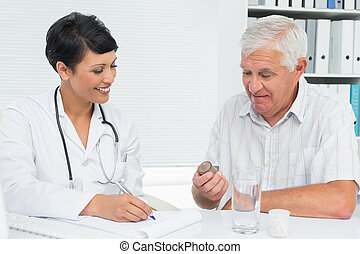 Doctor explaining reports to male patient - Female doctor...
