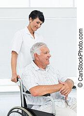 Nurse with senior patient sitting in wheelchair