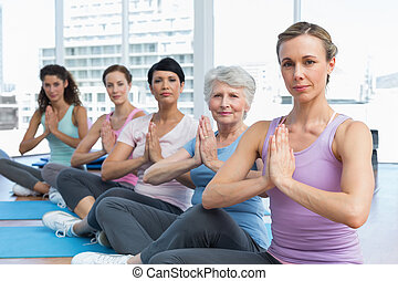 Class sitting with joined hands in a row at yoga class -...
