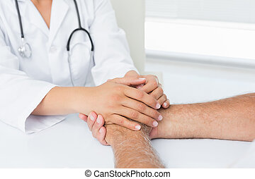 Close-up mid section of a doctor holding patients hands at...