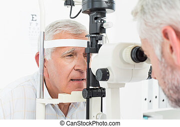 Optometrist doing sight testing for senior patient -...