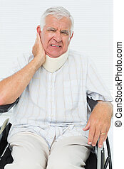 Senior man sitting in wheelchair with cervical collar -...