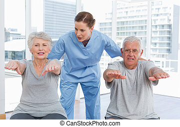 Female therapist assisting senior couple with exercises