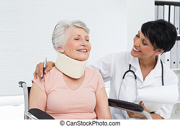 Doctor talking to a senior patient with cervical collar at...