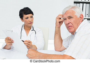 Doctor showing reports to worried senior patient - Female...