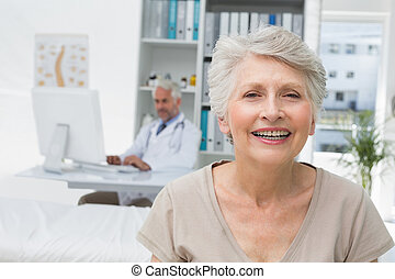 Happy senior patient with doctor at medical office