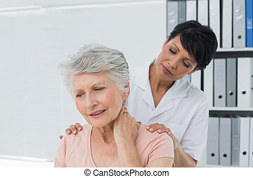 Chiropractor looking at senior woman with neck pain - Female...