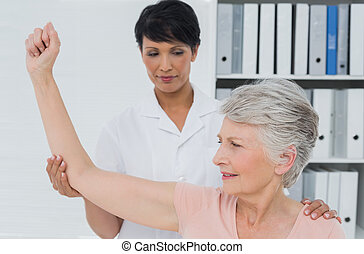 Physiotherapist assisting senior woman to stretch her hand -...