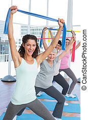 Class holding up exercise belts at yoga class - Happy female...