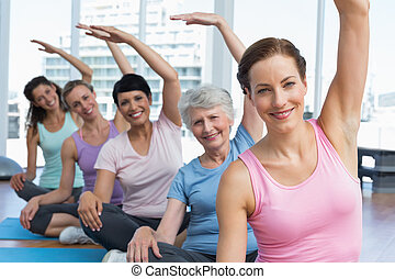 Trainer with women in row stretching hands at yoga class -...