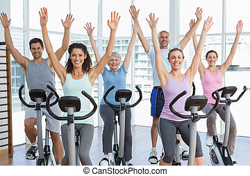 Happy people working out at spinnin - Group portrait of...